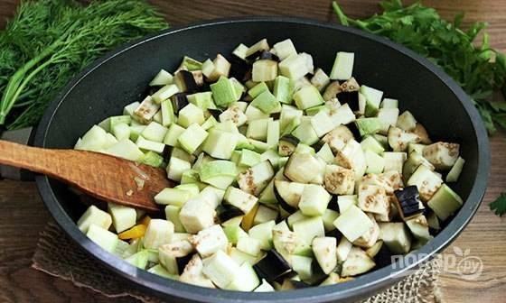 Потом добавьте баклажаны с кабачком. Готовьте овощи вместе ещё 3 минуты.