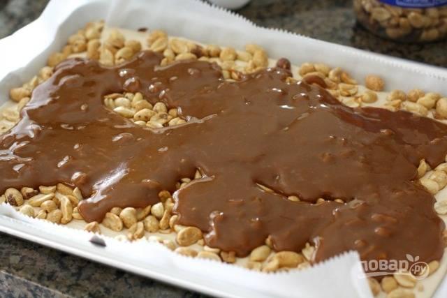 Ириски с оставшимися сливками отправьте в микроволновку, растопите и перемешайте. Достаньте форму, распределите на нугу орешки и слегка вдавите руками. Сверху вылейте карамельную массу. Отправьте в морозильник, растопите оставшийся шоколад с ореховым маслом, выложите на карамель и распределите.