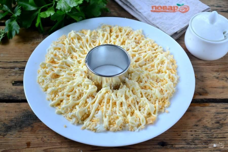 Начинайте выкладывать салат. Возьмите плоскую тарелку, в середину поставьте сервировочное кольцо. Вокруг кольца выложите яйца и смажьте майонезом.