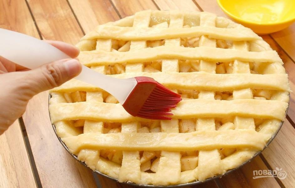 """Достаем форму с тестом из холодильника, равномерно распределяем начинку из яблок, при помощи полосок теста формируем """"сетку"""". Смазываем поверхность теста яйцами, взбитыми с молоком. Посыпаем корицей и отправляем в духовку. Выпекаем при 200 градусах в течение 15 минут, затем в течение 45 минут при температуре 180 градусов."""