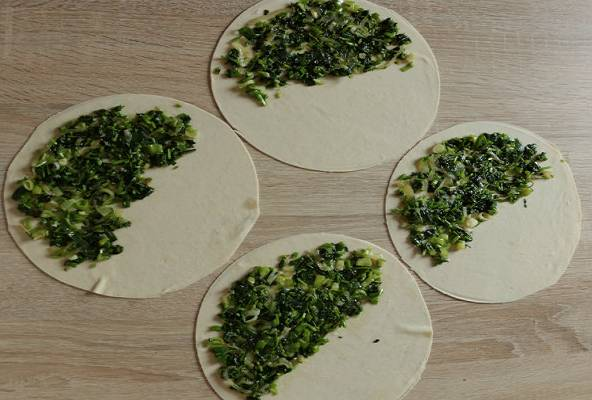 5. Сыр натереть на мелкой терке и добавить к зелени. При желании всыпать немного соли и перца. Перемешать и разложить начинку на одну половинку теста.