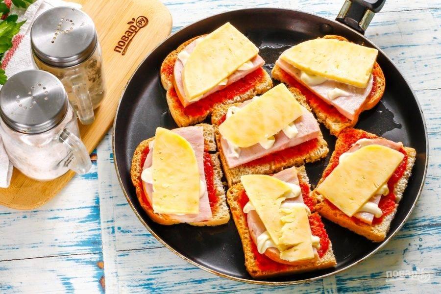Прогрейте сковороду с растительным маслом. Выложите в масло бутерброды и поджарьте их около 1-2 минут на умеренном нагреве. Затем влейте сбоку на сковороду воду и сразу же накройте емкость крышкой, нагрев уменьшите до минимального. Томите горячие бутерброды примерно 3-4 минуты, пока сыр не расплавится. Затем нагрев выключите.