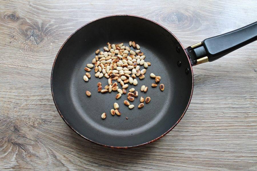 Поджарьте кедровые орешки на сухой сковороде до золотистого цвета.
