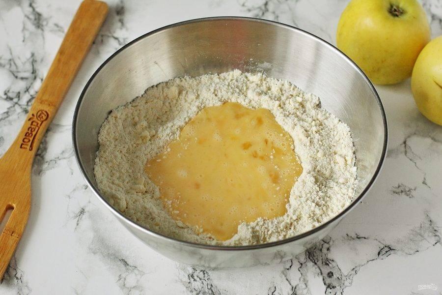 Перетрите руками до состояние крошек и добавьте взбитые вилочкой яйца.