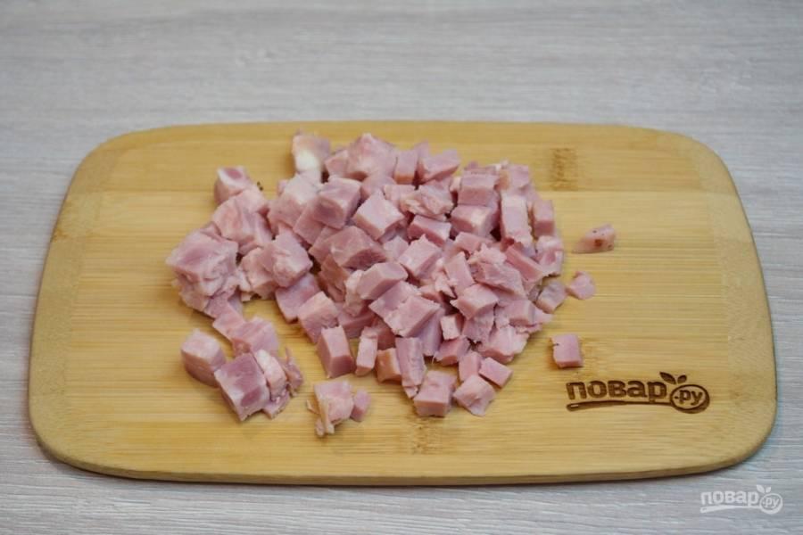 Для приготовления блюда я предлагаю взять ветчину. Есть варианты, когда блюдо готовится с обжаренной свининой, но вкуснее и эффектнее блюдо будет с использованием ветчины. Ветчину нарежьте кубиками.