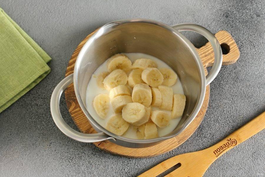 Бананы нарежьте кусочками и сложите в кастрюльку. Добавьте молоко.