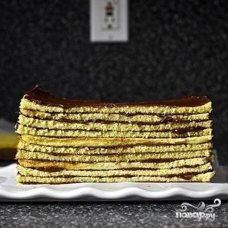 Укладывая смазанные кремом коржи один на другой, формируем торт. Смазываем кремом бока торта.