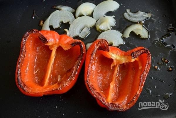 Лук нарежьте полукольцами. Перец разрежьте на две части, удалите плодоножку и семена.  Поместите на противень срезом вниз, полейте оливковым маслом и накройте фольгой. Запекайте овощи в разогретой духовке в течение 25 минут.