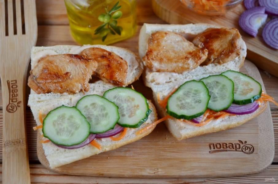 Смажьте соусом хлеб (обе половинки внутри). На одну половинку уложите маринованную морковь или дайкон, лук салатный, свежий огурчик, зелень приветствуется. На другую половинку багета положите жареное мясо.