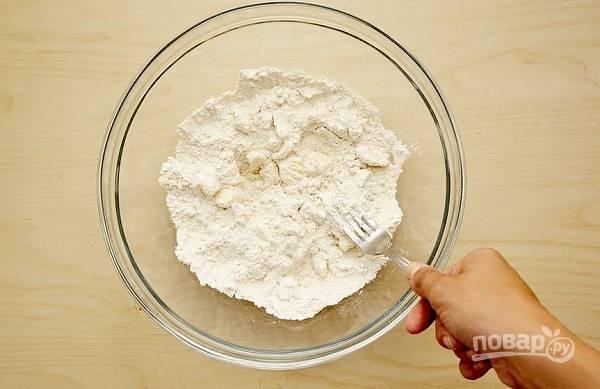 1. В глубокой мисочке соедините просеянную муку, соль, холодное масло и разомните вилкой до состояния однородной крошки. Влейте ледяную воду и замесите однородное тесто.