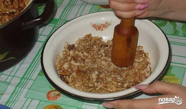 5. А пока можно заняться начинкой. Орешки подсушите пару минут на сковороде. Отберите жменю целых и отложите для украшения. Остальные орешки измельчите ножом.