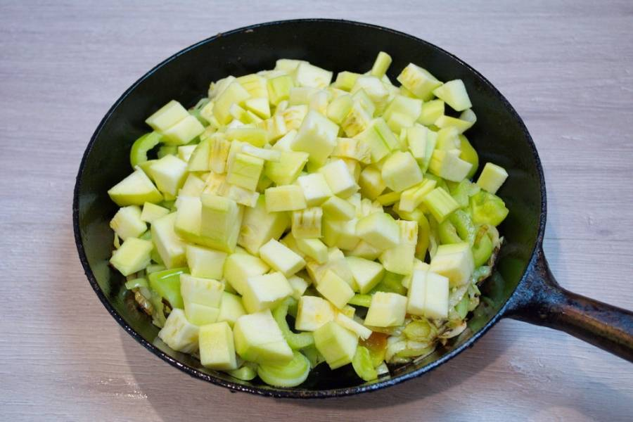 Болгарский перец вымойте, очистите и нарежьте некрупными кусочками. В сковороду к луку добавьте перец и кабачок. Перемешайте. Тушите овощи на небольшом огне. Сковороду можно накрыть крышкой.