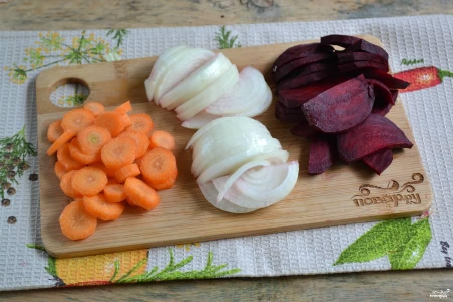 Морковь порежьте тонкими кружочками, свеклу и лук порубите полукольцами.
