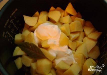 """Очистим и порежем картошку на кусочки. Не советую нарезать её мелко, иначе картошка разварится. Выкладываем картошку к мясу, наливаем стакан воды, добавляем сметану и лаврушку. Закрываем крышку мультиварки, включаем режим """"Тушение"""" или """"Выпечка"""". Тушим примерно 1.5 часа, на программе """"Выпечка"""" готовим меньше - минут 45-50. За 5 минут до окончания программы перемешаем мясо с картошкой и доготавливаем."""