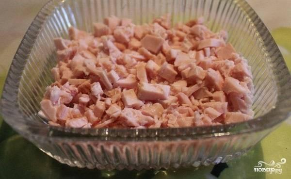 2.Половину куриной грудки измельчаем и укладываем на низ салатной формы, это будет первый слой. Смазываем тонким слоем майонеза.