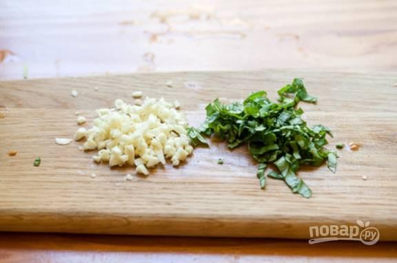 2.Очистите зубчики чеснока и нарубите их небольшими кусочками, измельчите зеленый базилик. Выложите все ингредиенты в блендер и измельчите.