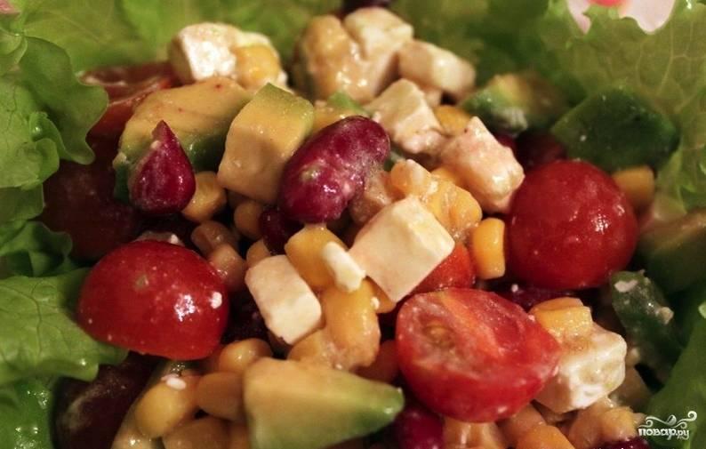 Вымойте и высушите листы салата. Когда все продукты подготовлены, выложите салат на дно пиалы, а затем положите туда остальные овощи и сыр, предварительно перемешав их в отдельной посуде. Сверху полейте всё заправкой и подавайте на стол.
