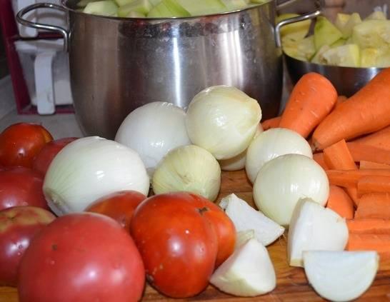 2. Затем вымойте помидоры, нарежьте их пополам или четвертинками. Очистите лук и морковь. Количество овощей, используемых в рецепте приготовления кабачковой икры на зиму на мясорубке, можете варьировать по вкусу.