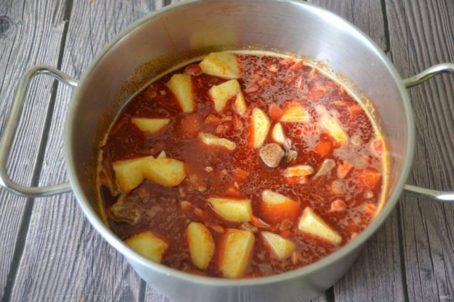 Переложите картофель к мясу и продолжайте тушить на небольшом огне час-полтора, ближе к концу варки добавьте острый перец чили.
