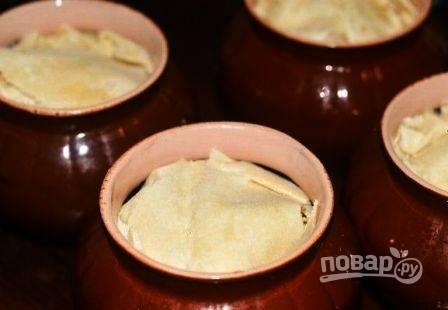 Тонкий лаваш нарезаем на кусочки, накрываем ими картошку в горшочках. И ставим всё запекаться при 180 градусах в духовку.
