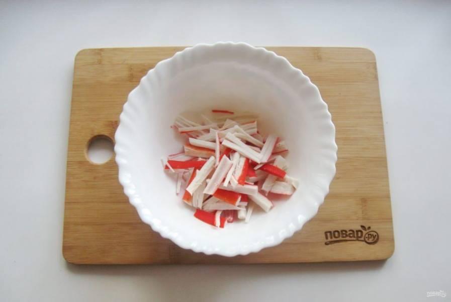 Крабовые палочки нарежьте тонкой соломкой.