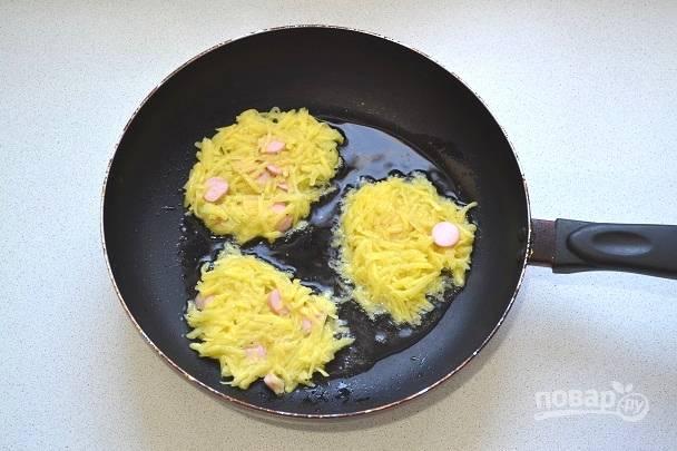 На сковороде разогрейте растительное масло. Ложкой выкладывайте картофель на сковороду ровными оладьями.