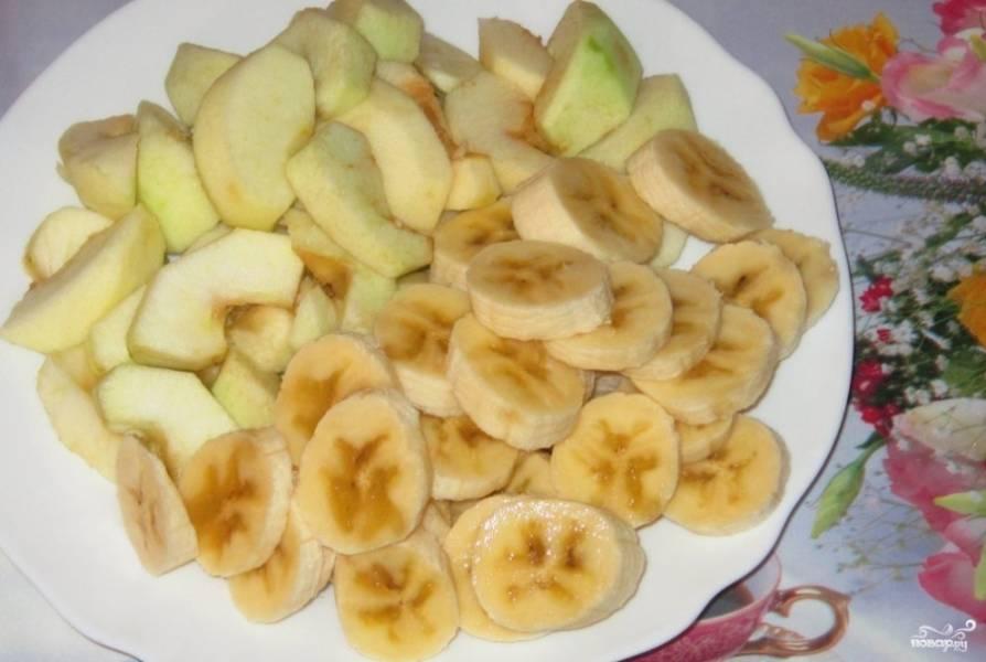 Бананы с яблоками помойте и высушите. Бананы очистите от кожуры, из яблок достаньте сердцевину. Фрукты нарежьте небольшими кусочками.