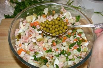 Смешиваем подготовленные ингредиенты в салатнице, засыпаем горошек (без жидкости) и солим по вкусу. Заправляем салат майонезом, перемешиваем.