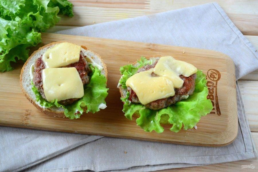 Каждую булочку разрежьте пополам. Положите половинки булочек местом разреза на сковороду гриль и слегка поджарьте, можно просто подсушить на сухой сковороде. А можно совсем не поджаривать, если вы любите более мягкие чизбургеры. Нижнюю часть булочки смажьте небольшим количеством майонеза или соуса, положите лист салата. Сверху положите готовую котлету с сыром.