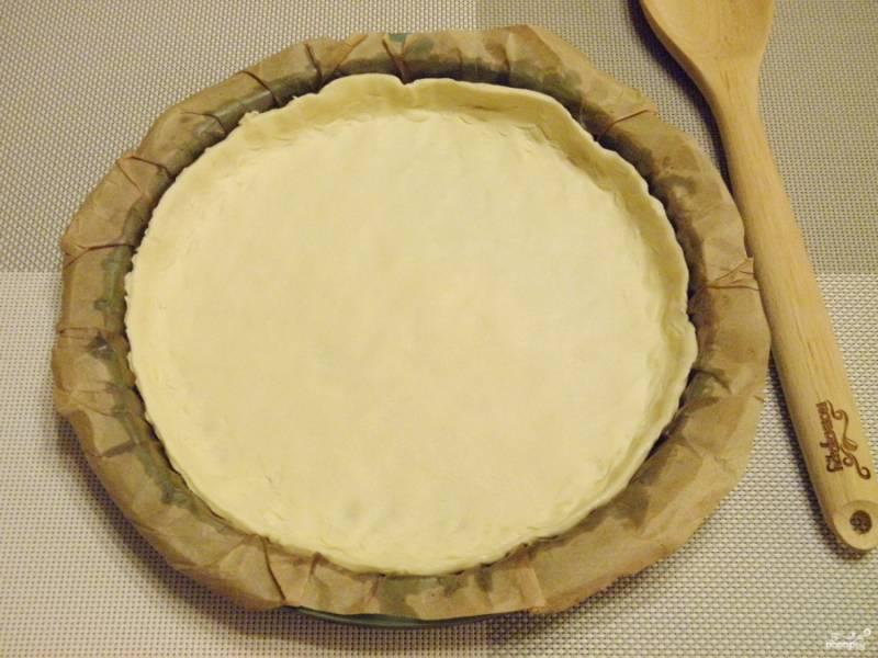 Возьмите невысокую форму. Застелите её бумагой и смажьте растительным маслом без запаха. Тесто пальцами разровняйте по форме, формируя бортики.