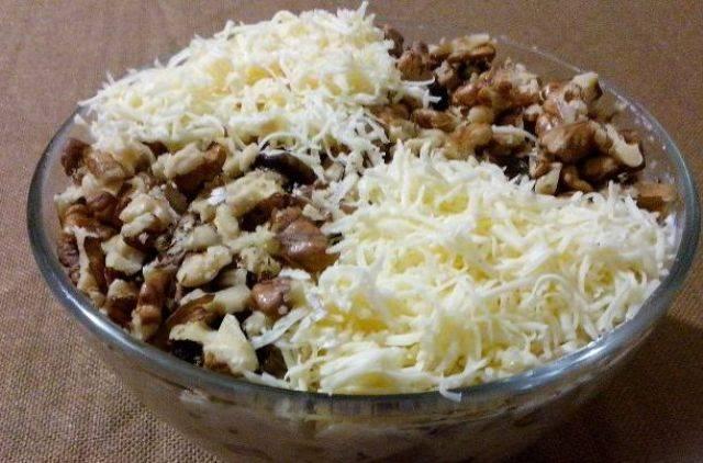 Украшаем наш салат оставшимися грецкими орехами и тертым сыром. Готово!