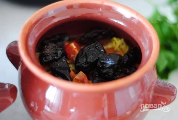 3. На дно горшочка выложите курицу. Затем отправьте туда предварительно обжаренные овощи. Добавьте пропущенный через пресс чеснок и вымытый чернослив.