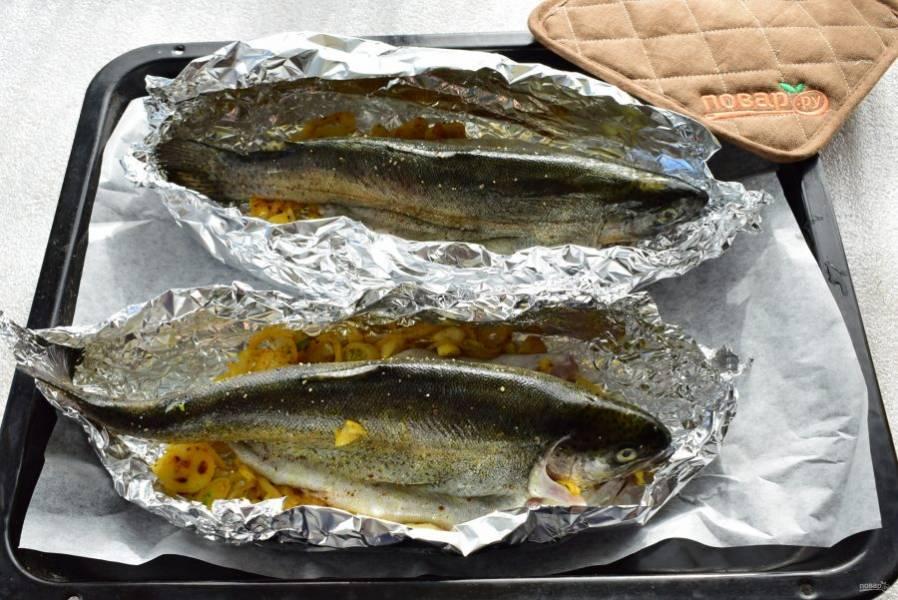 На противень положите лист пергамента для выпечки, фольгу. На дно фольги выложите луковую подушку, сверху – форель, расположив ее на животе. Из фольги сформируйте лодочки так, чтобы она не касалась рыбы. Поставьте запекаться в разогретую до 180-200°C духовку на 20-25 минут.