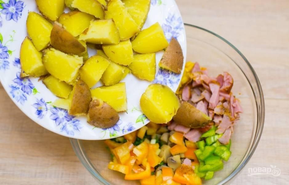 Картофель почистите и крупно нарежьте. Если картошка молодая, то можете её не чистить. Добавьте её в салатницу.