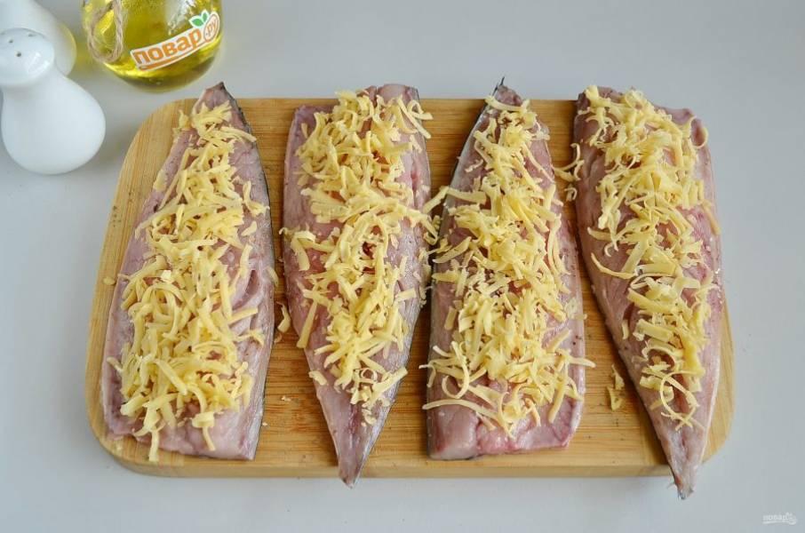 5. Посыпьте щедро рыбу сыром. Можно тертый сыр заменить на пластинки, подогнав их по размеру тушек.