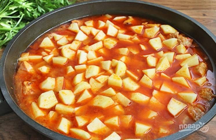 Также закладываем очищенный и порезанный кубиками картофель, солим и перчим. Тушим минут 25 до мягкости картошки.