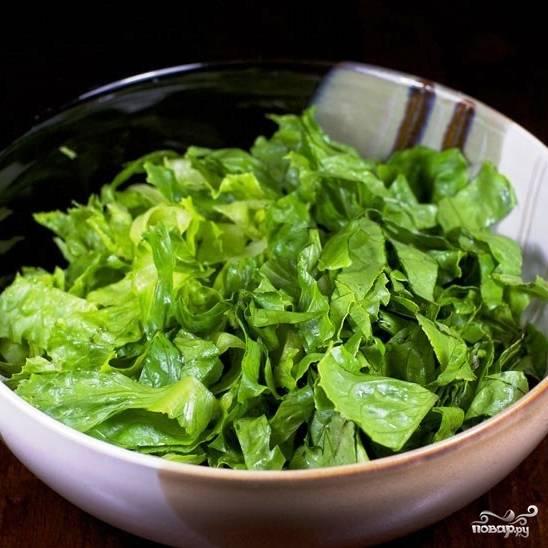 Листья салата тщательно промываем, крупно рвем руками и кладем в салатницу.