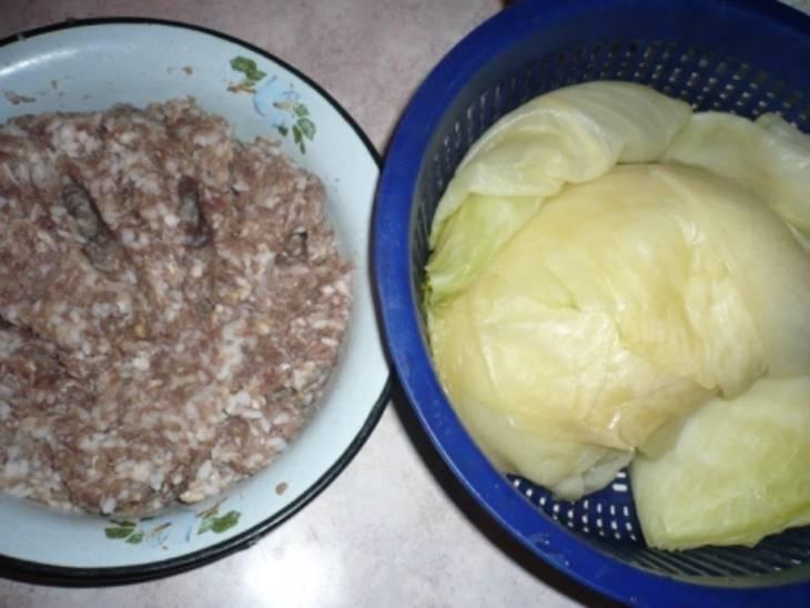 Отварите до полуготовности листья капусты, дайте им стечь. В фарш добавьте рис, тоже отваренный до полуготовности. А также измельченный лук, специи. Все перемешайте.