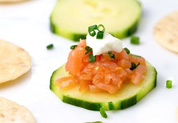 3. Выложите по ложке тартара на крекер или ломтик огурца. Присыпьте зеленью и по желанию дополните сметаной. Приятного аппетита!