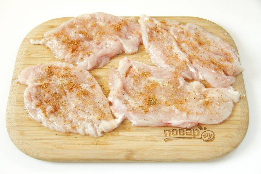 Куриную грудку нарежьте вдоль на порционные кусочки, отбейте молоточком, посолите по вкусу и посыпьте специями.