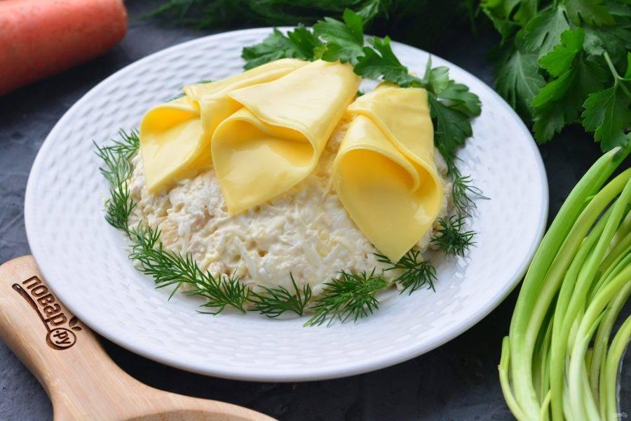 """Сверните пластинки плавленого сыра и придайте им форму цветов — получаются """"каллы"""". Выложите """"каллы"""" на салат."""