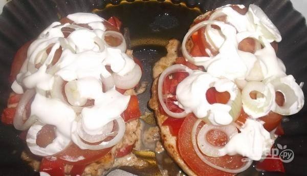 Затем, не выключая духовки, достаньте грудку. На неё слоями уложите перец, помидоры, лук и немного сметаны. Запекайте блюдо ещё 20 минут.