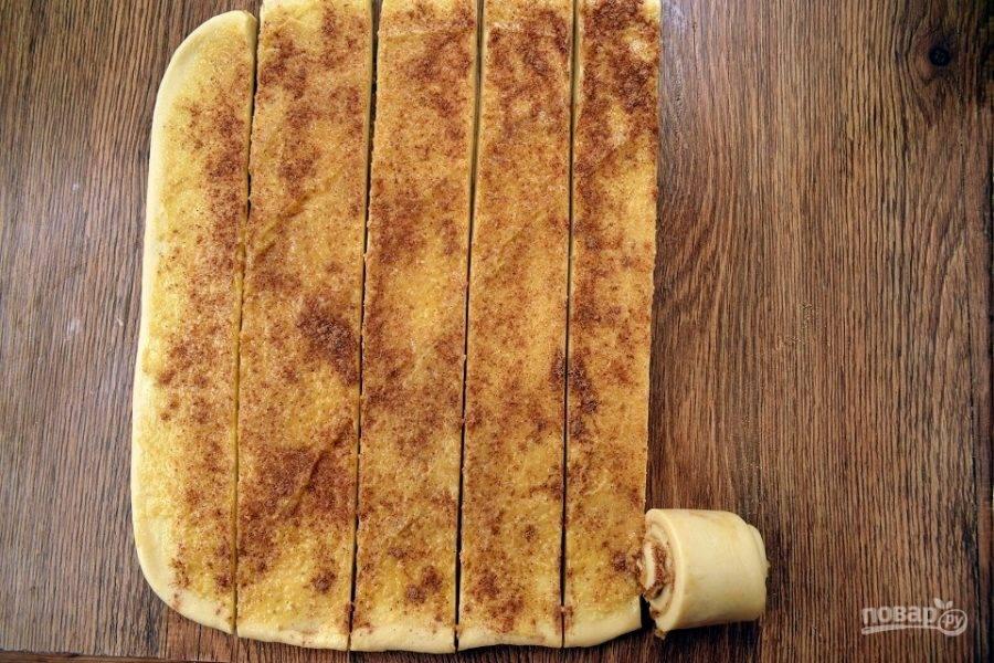 Тесто с орехово-коричной начинкой разрежьте вдоль на 6 равных по ширине полоски. Одну полоску сверните рулетом.