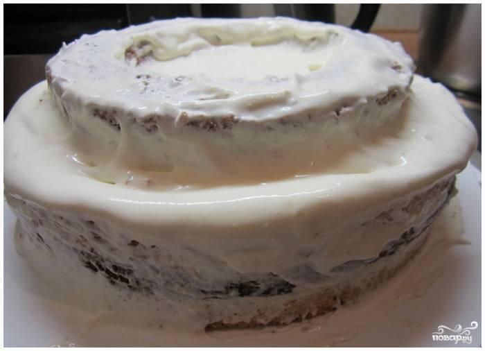 Шаг 10. Возьмите средний круг от коричневого бисквита, поместите его посередине торта. Хорошо смажьте кремом.