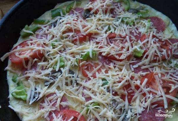 5.Приготовьтесь к формированию пиццы. Раскатайте корж. Смажьте противень маслом. Положите на него корж. Помажьте майонезом, смешанным с ткемали. Уложите поверх коржа начинку. Сверху аккуратно рассыпьте сыр.