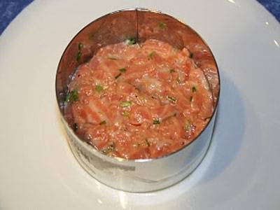 8. Выложить на тарелку сервировочное кольцо. Отправить в него немного рыбы (если специального кольца нет, то лосось с сыром в домашних условиях можно сделать с помощью банки от консервированного горошка или кукурузы, например, предварительно обрезав дно). Сверху выложить сырную начинку. Дополнить такое блюдо можно зернами икры или свежими овощами по вкусу.