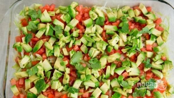 8.Чищу авокадо, мою помидоры (большие) и нарезаю все небольшими кусочками. Салат режу мелко. Сперва выкладываю слой салата, томатов, затем — авокадо. Посыпаю мелко рубленой кинзой.