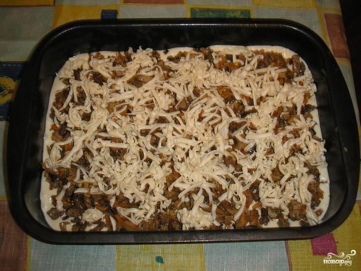 Форму для выпечки смажьте растительным маслом. Поставьте духовку разогреваться, выставив температуру на 180 градусов. На дно формы налейте половину теста, выложите на тесто начинку, а сверху натрите охлаждённый плавленый сыр. Затем налейте вторую часть теста.