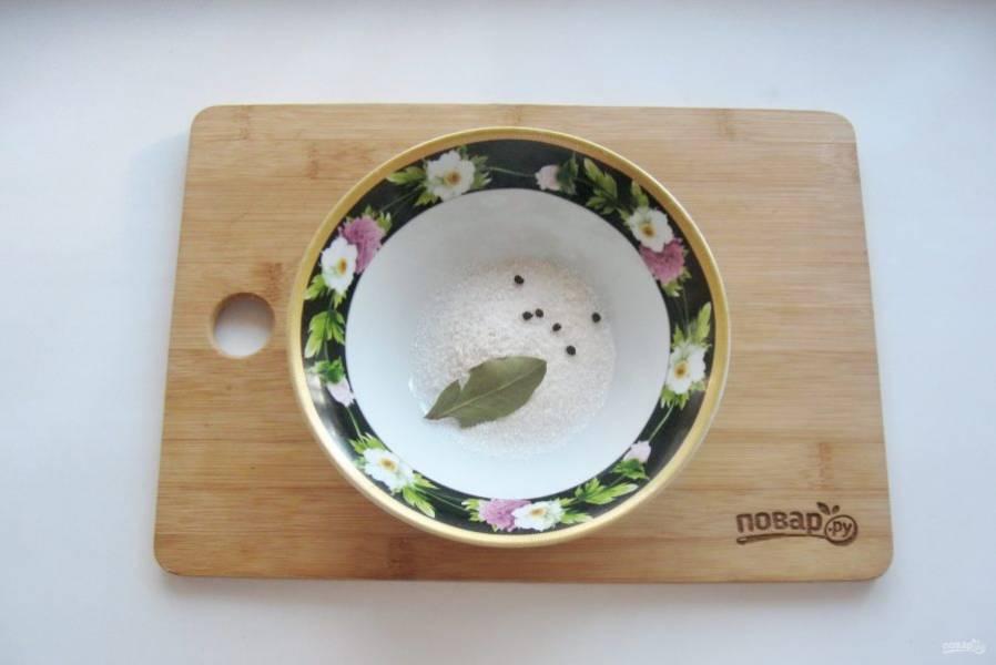 Приготовьте маринад. В миску или тарелку выложите соль, сахар, черный перец горошком и лавровый лист.