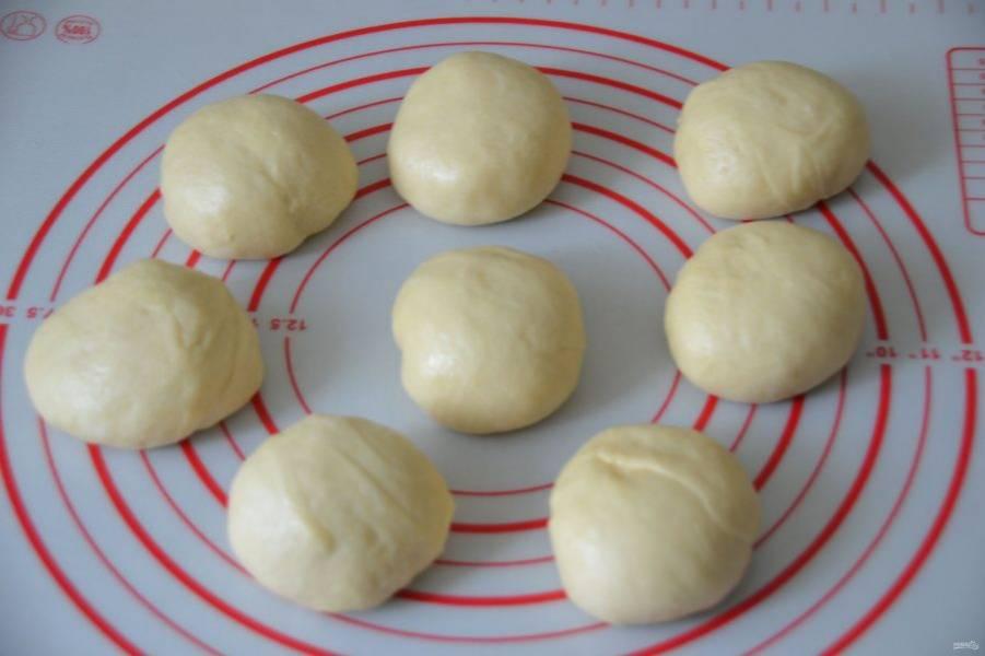 Разделите тесто на 8 равных частей весом около 80 грамм. Подкатайте их в шар. Накройте пленкой и оставьте в покое на 5-7 минут.